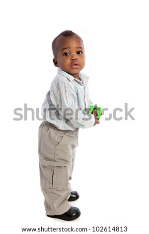 1 year old baby boy standing holding a soft toy ball on isolated background