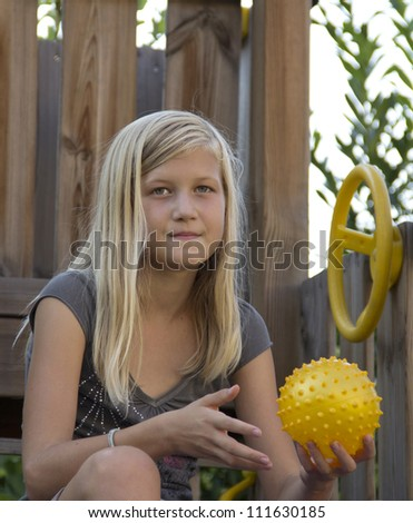 11-year-old blond girl with yellow ball, sitting on a wooden playground