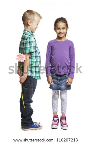 8 year old boy giving pink flower to girl on white background