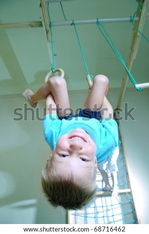 5 year old boy hanging on gymnastic rings