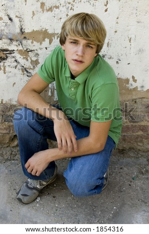 stock photo : 15 year old boy outside against old wall. Blonde hair, blue