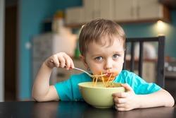 3 year old boy while eating spaghetti