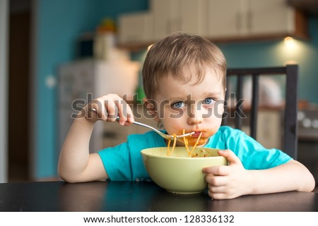 3 year old boy while eating spaghetti