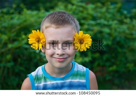 8-year old boy with flowers on ears having fun