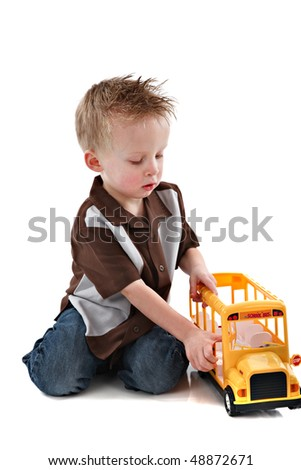 4 Year Old Caucasian Boy Plying with Yellow School Bus Toy on White Background