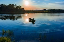 60-year-old Caucasian man with a fishing rod in his hands fishes in a boat with a motor at sunset on the lake