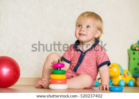 1,5 year-old child playing with educational cup toys at home. Little blond baby boy with blue eyes is learning to play with pyramid toy on the floor. Little kid have fun indoors