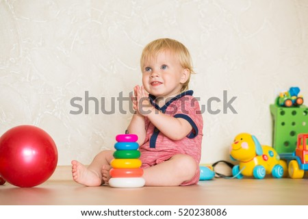 1,5 year-old child playing with educational cup toys at home. Little blond baby boy with blue eyes is playing with pyramid toy on the floor. Little kid have fun indoors
