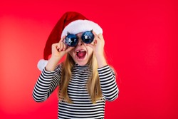 8 year old girl in santa hat covering her eyes with blue baubles. Studio photo on red background.