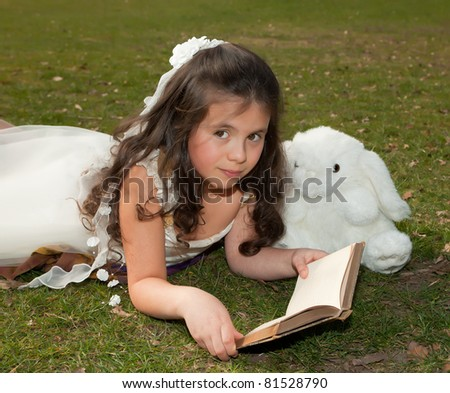 7 year old girl reading a book on grass