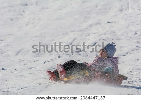 5-year-old girl riding a balloon from a snow slide