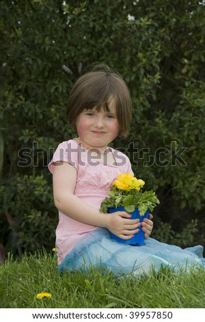 4 year old girl sitting in grass and holding flower  MR