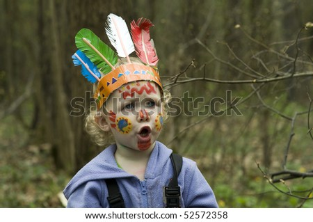 2-Year-Old Girl with the face paint  playing indian outdoors