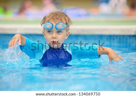 2 year old kid laughing in a swimming pool