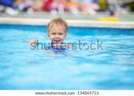 2 year old kid laughing in a swimming pool.