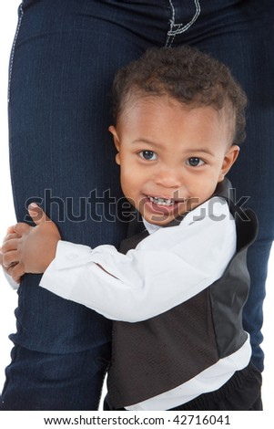 2 year old little African American boy holding Mom's leg standing