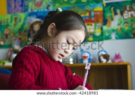 8-year old little asian girl doing homework; low angle view