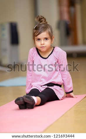 5 year old little girl doing sports exercises on the mat