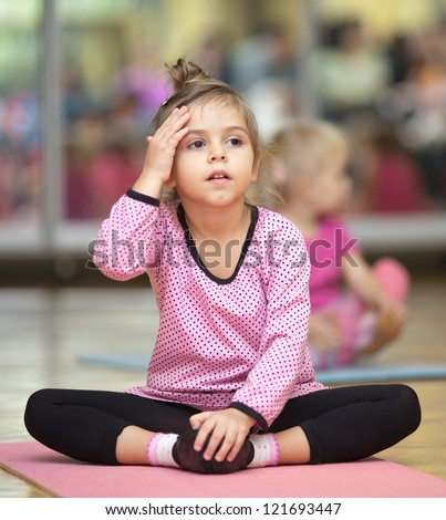 5 year old little girl sitting on the mat at dacing lesson