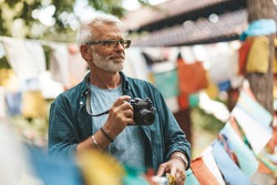 60-year old man active trekking in Nepal, photographer explores the national culture. Elderly person in travel, healthy lifestyle of pensioner.