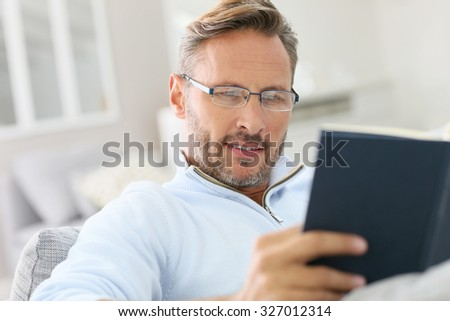 40-year-old man relaxing in sofa reading book