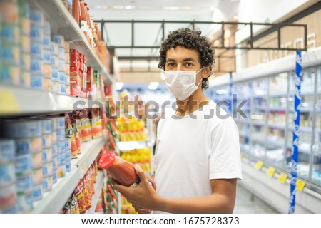 22-year-old man with protective mask makes purchase in supermarket