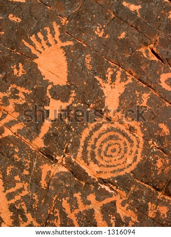3,000 year old Native American petroglyphs carved in red sandstone in the southwestern USA desert.
