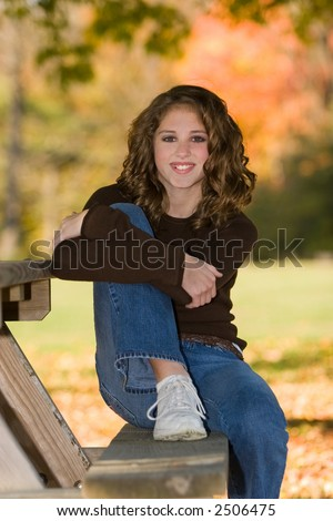 stock photo : 12 year old pre-teen girl on picnic table bench under a