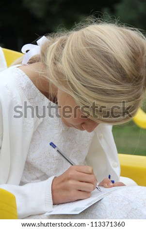 11-year old pretty blond girl in white dress, writing her best wishes on a card at a wedding