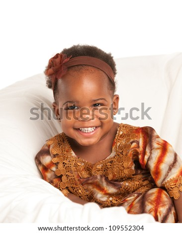 3 year old Smiling  African American girl in Colorful Costume sit on bed