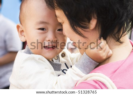 2-year old toddler in young asian mother's arms.