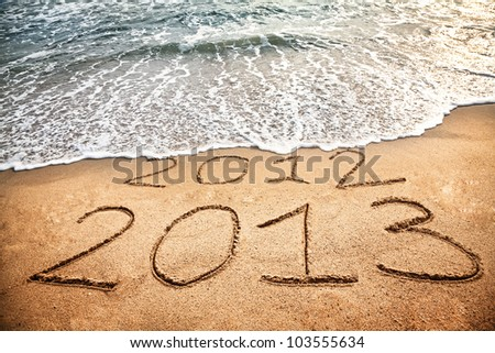 2013 year on the sand beach near the ocean. 2012 is been erasing by wave #103555634