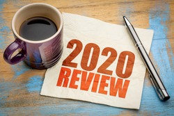 2020 year review text on a napkin with a cup of coffee, end of year business concept