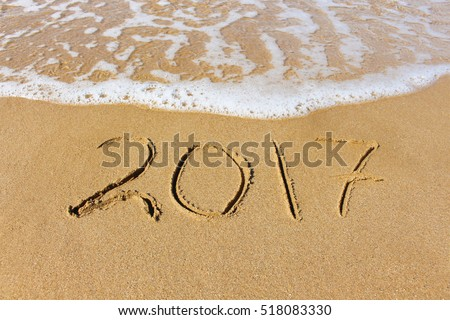 2017 year written on sandy beach sea  #518083330