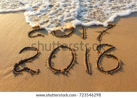 2018 year written on sandy beach sea. Inscription 2017 washes off wave. #723546298