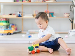 2.5 years baby boy.Little child boy playing stack with colorful wooden toys block alone.Kids play with educational toys at home.Day care and Kindergarten school.child development concept.