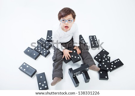4 years boy with Down Syndrome playing with domino game on white background