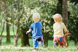 3-4 years joyful boys riding a balance bike (run bike). Happy children learning to wheel, keep balance on training bicycle in the park. Active kids have a walk and play outside.
