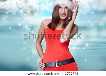 20-25 years od beautiful woman in christmas dress posing against winter background