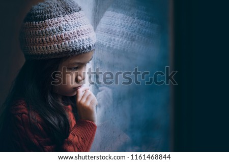 6 years old Asian girl sad by the window in winter red sweater and knitted hat.Cold weather make condensation on window glass,girl draw sad face on it.Concept of sad child.Preteen lifestyle.