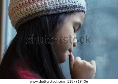 6 years old Asian girl stand by the window.Girl sucking her thumb,closed her eyes.Thumb sucking is a normal habit for babies and young children,comforting gesture or relaxing for child.