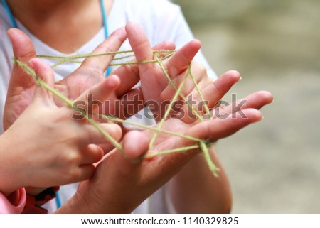 5-6 years old  Asian little girl playing string game with her mother.Hands Playing String Game Creativity.A popular string game is cat's cradle or rabbit's cradle.Girl enjoy and fun.Creative thinking.