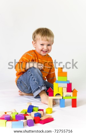 2 years old baby boy playing with wooden blocks.