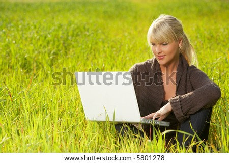 20-25 years old beautiful sexy woman portrait working on laptop computer on green grass meadow