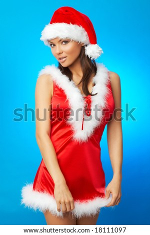 20-25 years old beautiful woman in Santa Claus hat on blue