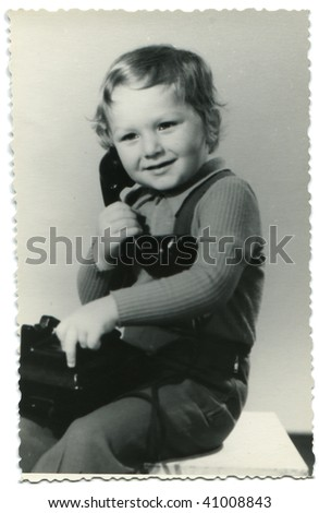 3-years-old boy calling by phone, posing in the studio; old photo taken in 1976