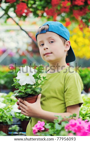 7 years old boy in his flower garden - kids and family