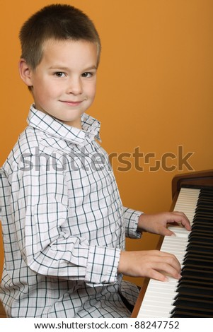 6 years old boy is playing the piano