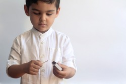5-6 years old boy playing with fire. Middle eastern kid exploring fire. First tries of a child to play with match sticks. Copy space
