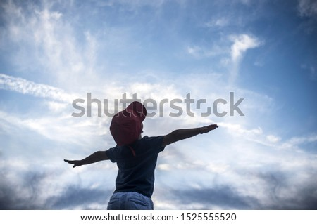 4 years old boy pretending to fly over cloudy sky. Encourage children Imagination concept #1525555520